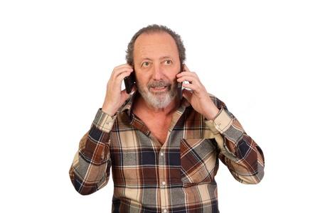 Homme parlant sur deux t�l�phones cellulaires Banque d'images