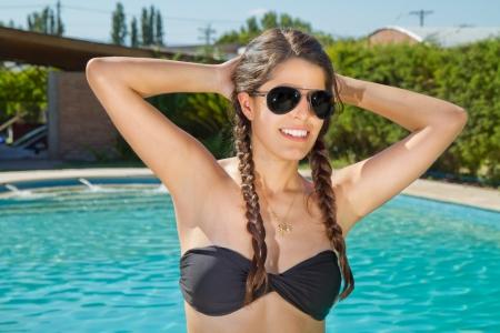 Belle jeune femme sexy en bikini noir debout � c�t� de la piscine