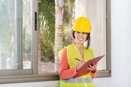 Woman holding a notepad and writing at work in a construction
