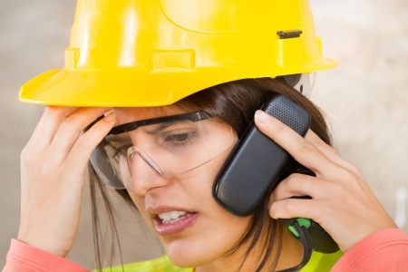 Portrait of a woman with safety helmet and mobile phone