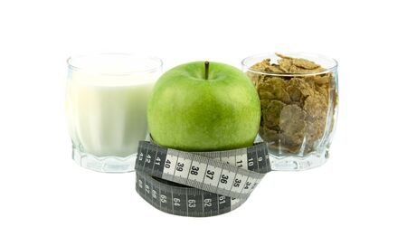 A green apple and a black and white measuring tape, oatmeal, kefir, cereal, very tasty. Archivio Fotografico