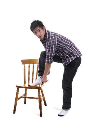 strip shirt: Guy removing his sock Stock Photo