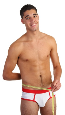 man in underwear: A guy using a tape measure to measure his waist Stock Photo