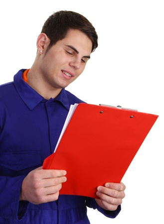 A guy in blue boilersuit looking at a clipboard photo