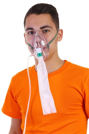 A young guy in an orange shirt wearing an oxygen mask Stock Photo