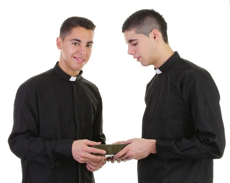 A priest passing a bible to another priest photo
