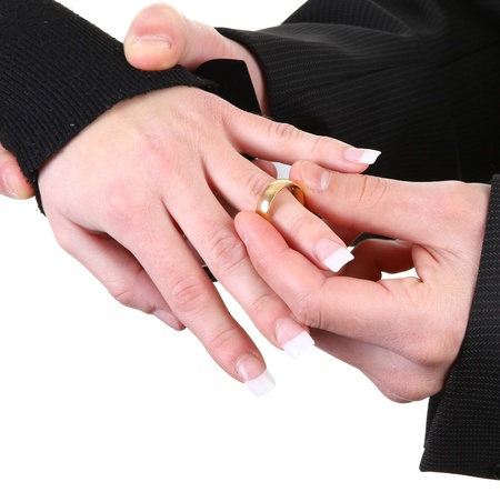 A guy putting a ring onto a girls hand photo