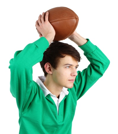 A rugby player holding the ball above his head isolated on white