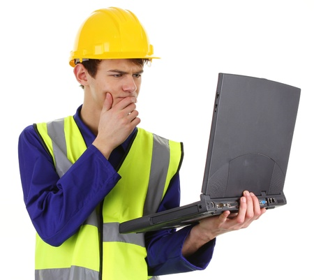 A construction worker with a laptop isolated on white photo