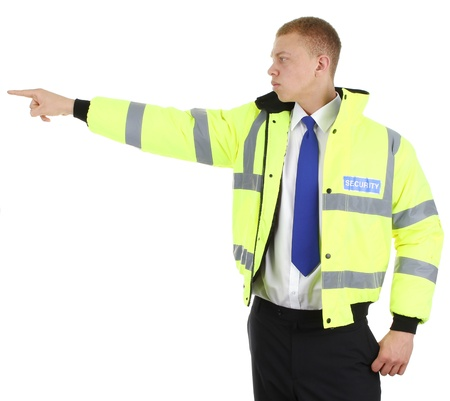 A security guard with a serious expression pointing