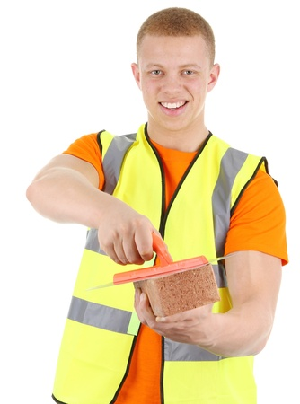 A guy holding a brick and a trowel. Isolated on white photo