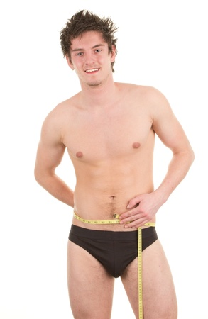A guy holding a tape measure around his waist, isolated on white photo
