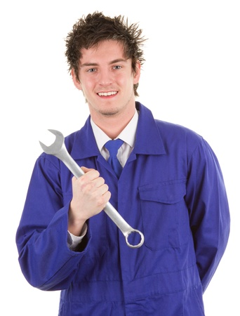 A car mechanic in blue overalls holding a spanner, isolated on white