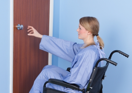 A disabled person struggling to open a door by themself photo