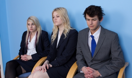 three individuals waiting outside an office door for a result Stock Photo