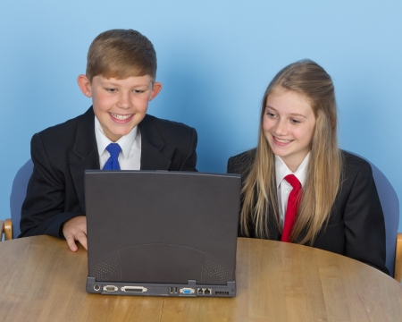Two children working together on their schoolwork using a laptop Stock Photo - 14873906