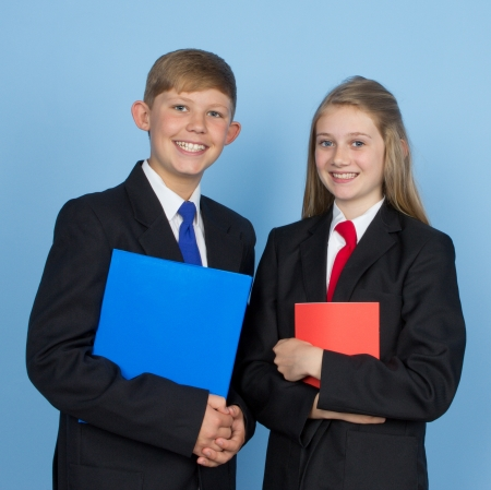 Two school children holding books, against a blue backing.