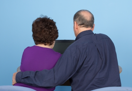 A rear view of an elderly couple using a computer together, against a natural blue background photo
