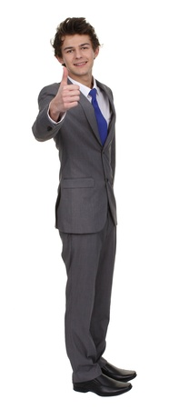 Businessman full length isolated with a thumbs up sign, selective focus on thumb. photo