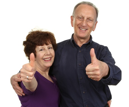 An elderly couple showing a thumbs up sign, isolated on white  photo