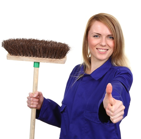 A young woman holding a broom, with a thumbs up sign, isolated on white photo