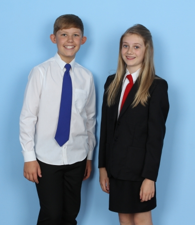 Two school children standing in uniform against a blue background photo