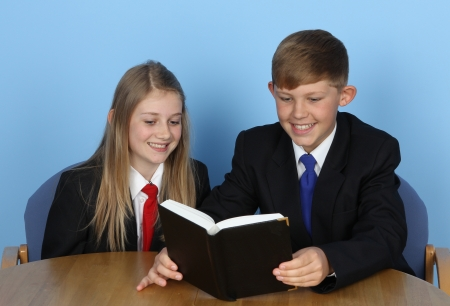Two school children sitting at a desk, reading a book against a blue background. photo