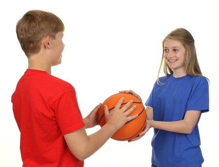 Two children playing basketball, isolated on white. photo