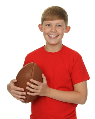 A child standing, holding a rugby ball, isolated on white.
