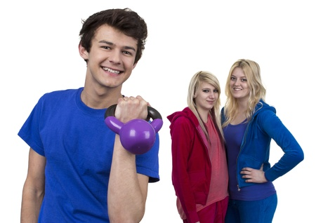 Young Man Holding Weight  In Front Of Two Women Over White Background photo