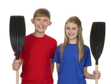 canoe paddle: Portrait Of Boy And Girl Holding Canoe Paddle Isolated Over White Background Stock Photo