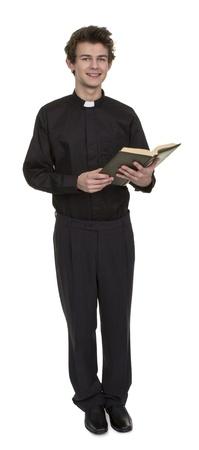 predicador: Sacerdote joven que sostiene la Biblia sobre el fondo blanco Foto de archivo