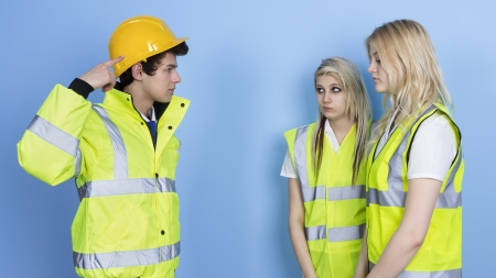 Man Shouting To Female Worker For Not Wearing Hard Hat Over Blue Background photo