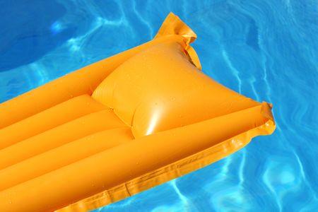 swimmingpool: yellow airbed floating in swimming-pool Stock Photo