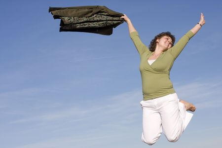 Happy woman jumping in the sky, happy because spring is coming Stock Photo