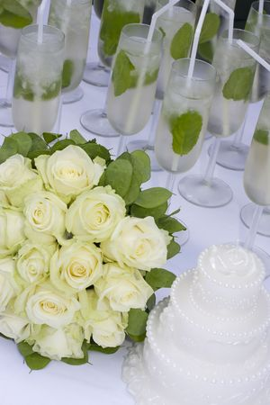 bridal bouquet with cake and champagne on white table