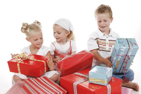 three cute children celebrating special occasion with several gifts photo