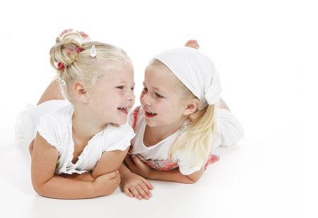 two cute little girls dressed in white being best friends