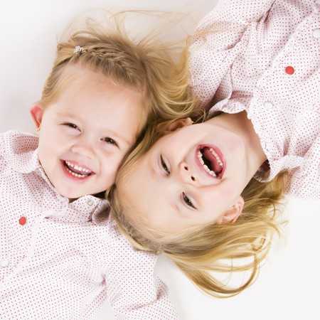 infants: two cute twin sisters having fun