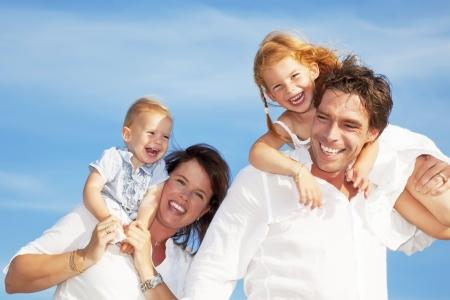 uomo felice: famiglia di giovani felici divertimento all'aria aperta, vestita di bianco e con il cielo blu sullo sfondo