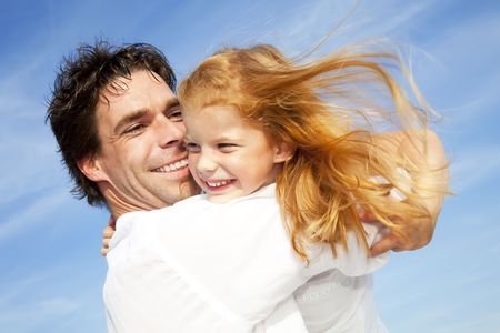 father and daughter having fun outdoors, dressed in white and with blue sky in background Stock Photo