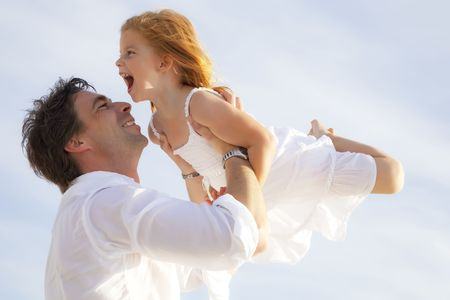 father and daughter having fun outdoors, dressed in white and with blue sky in background photo