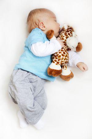 white blanket: newborn baby sleeping, holding teddy bear on white blanket