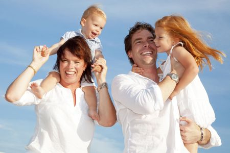 young happy family having fun outdoors, dressed in white and with blue sky in background Stock Photo - 6571090