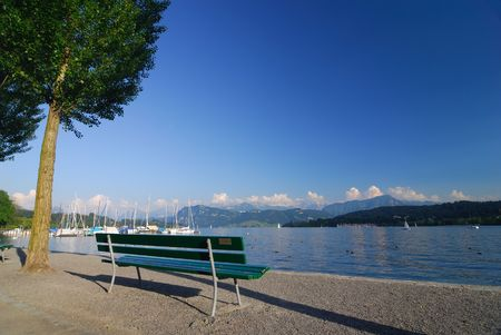 A bench in the Swiss Alps by Lake Luzern Stock Photo
