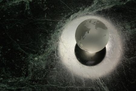 A glass earth orb with a halo on a 'universe' background Stock Photo - 18388971