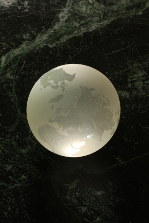 A glass earth orb on a universe background Stock Photo