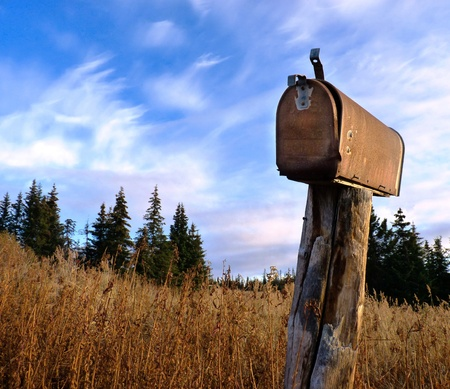 A rusty old rural mailbox on a wooden post in dry grass with spruce in the background and a bright blue sky with clouds