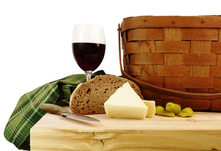 A vintage picnic basket with a glass of red wine, cheese, and bread on a rustic pine table with a pure white background Stock Photo - 9024660