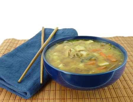 A healthy bowl of hot miso soup with tofu and vegetables on a bamboo mat with chopsticks on a pure white background Stock Photo